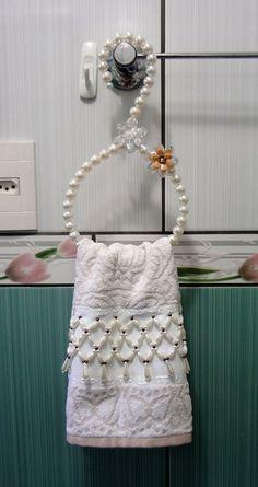 O Kit contém:  01 toalha de lavabo bordada em pedraria (karsten) medida 33 x 50.  01 porta papel higiênico bordado em pedraria, medida 12 x 48.  01 cabide feito em pedraria, medida 16 x 28.