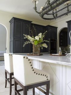 nailhead trim bar stools. love the molding design on the counter front too.