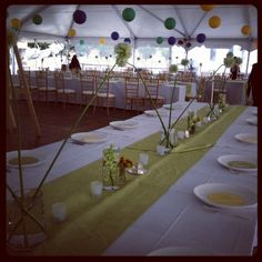 Here we did a mix of yellow, green and blue lanterns at the Ronald Reagan Building in Washington, DC.  These long tables had fun white aliums, submerged green cymbidium orchids and billy ball arrangements in vintage vases - www.eleganceandsimplicity.com #wedding #DC