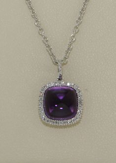 18Kt. white gold Diamond surround style pendant mount, open filigre construction and set with 1 @ 3.61ct. square sugar loaf style encabochon cut Natural Quarts, fine Amethyst and 0.13cts. total weight of small round brilliant cut Diamonds.