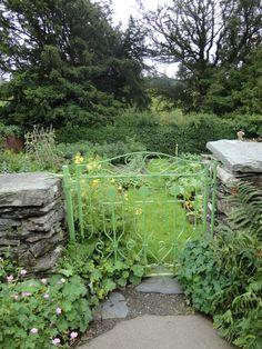 Through the green wrought iron gate into the garden at Beatrix Potter's Hill Top Farm. Near Sawrey, Cumbria Lake District, England, UK