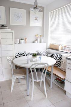 Jasna jadalnia z białym okrąglym stołem i białymi krzesłami. Dekorację stanowią tu poduszki w czarno – białe,...