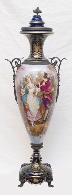 17 - SEVRES HAND PAINTED COBALT PORCELAIN & BRONZE URN A stunning and large antique Sevres hand painted cobalt French porcelain urn depicting landscape scenes. Bronze mounted handles and foot. Signed Porevie. Bottom holds blue Sevres mark. Measures approx. 42 height (107.7cm).