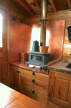 Andrews Tiny House - Wagon - Ideas of Wagon - Marine wood-burning stove in this small kitchen. That copper back piece is pretty cool too. Tiny House Swoon, Tiny House Living, Tiny House On Wheels, Small Living, Mini Loft, Gypsy Caravan, Tiny Spaces, Off The Grid, Little Houses