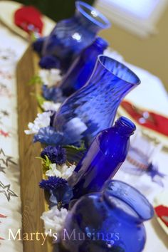 Using blue bottles and a DIY fence slat box to make an amazing centerpiece. From Marty's Musings