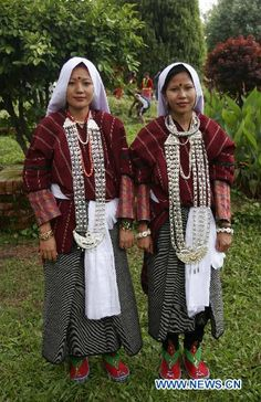 "Two Nepalese indigenous girls from Baisy Sauka of far western Nepal wearing their traditional dress and ornaments called ""Chandrahar"" pose for photos during the World Indigenous Day rally in Kathmandu, capital of Nepal, Aug. 9, 2010. (Xinhua/Bimal Gutam)"