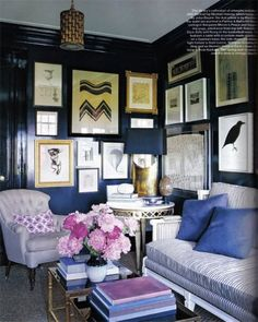 midnight blue walls offset by the light couches and peonies.