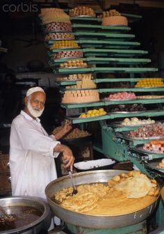 """A food shop in the Bazaar in Peshawar, Pakistan. The Kanishka merchants used to come here to do business in the daytime, and at night they would go to an inn, sit around a fire, sip Qahwa, and tell stories. Thus the bazaar got its nickname """"the Bazaar of Story Tellers."""""""