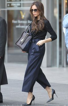 Victoria Beckham in New York shopping post her runway shows... love the tailored navy trousers with front french pleat and no belt, the over-sized handbag, and the black stilettos!!