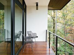 Wire chairs by Rejuvenation and pendantsby Hinkley Lighting grace the balcony outside.    This originally appeared in Minimal North Carolina Home Built for a Tech-Forward West Coast Couple.