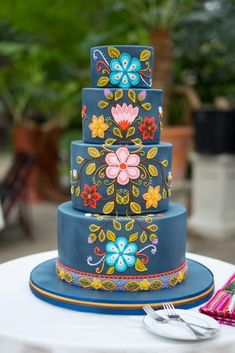 Royal Blue tiered wedding cake with bright summer flowers