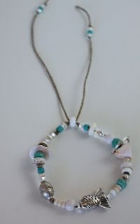 item #B071 Sink or swim- bracelet is inspired by the ocean and all the fish that live beneath the surface that we see- made of antique trinkets, silver rings, sea shells, bone beads, puka shells, and silver plated beads, antique african beads, and clear, white, turquoise glass beads all beaded on a natural cord.