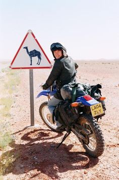 Lois Pryce in Morocco next to a road sign depicting a camel