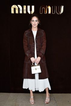 Matilda Lutz wears a white midi dress with a brown suede coat, top-handle bag, and metallic heels