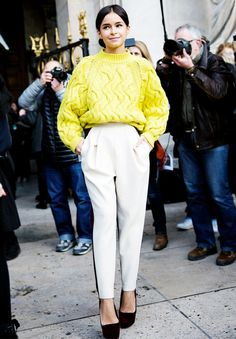 Miroslava Duma pairs a bright chunky sweater with tailored cream tuxedo trousers and platforms.