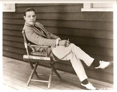 Exterior publicity shot of Rudolph Valentino relaxing in a film set chair on the Paramount lot.