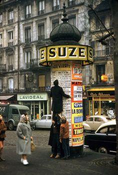 Une colonne Morris, place des Abbesses, 1957. Créées en 1868 par l'imprimeur Gabriel Morris, ces édifices cylindriques servent de support pour l'affichage théâtral et cinématographique. Elles ont progressivement disparu des rues parisiennes... (photo par Robert Doisneau - en couleur, ce n'est pas si fréquent!).  Paris d'antan, Facebook
