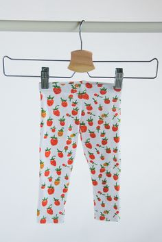 Heather Ross knit orange berry leggings. With a folded elastic waistband. **Made to order. Allow 1-2 weeks to ship.**Care: Garment has been pre-washed and pre-shrunk with unscented, phosphate-free detergent. Machine wash on delicate cycle. Tumble dry on low or lay out to dry. Press with warm iron if desired.