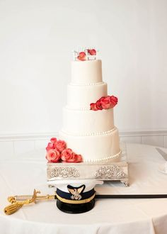 A nautical themed wedding cake is offset by the groom's sword & combination cap.