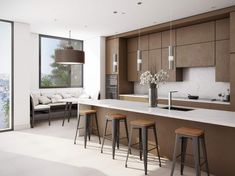 Spacious single wall with island modern kitchen done in medium brown and white. The non-hardware cabinetry give it a modern flare along with the engineered quartz countertops, waterfall island and chrome pendant lights. Check out that awesome dining nook with bench off to the side.