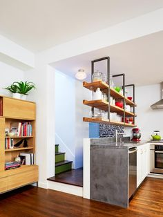 The Brooklyn-based design firm General Assembly hung shelves anchored into a steel plate in the ceiling joists in this 300-square-foot duplex to provide extra storage while maintaining a connection to the upstairs.