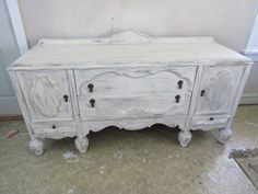 Early 1900s Jacobean buffet sideboard, painted creamy white with grey distressed highlights on medallion doors, 2 deep center drawers, and small drawers under side doors. Original hanging hardware, large pineapple feet.  Dimensions: 73 L X 22 D X 35 H (40 H with back crown, 75 L foot to foot)  SHIPPING NOT INCLUDED, PLEASE CONTACT US WITH PHONE # FOR QUOTE.  Local pick up always welcome, we can often make arrangements with those who are in the eastern corridor for delivery, 2 Hours +/- o...