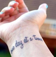one day at a time. wrist word tattoo