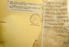"""National Archives of India: A farman or imperial directive issued by Mughal emperor Aurangzeb lies in a torn folder. The label reads, """"It is very badly damaged and broken at places."""""""