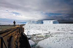 John Palmer, the resident doctor onboard the icebreaker Kapitan Khlebnikov, watching two icebergs about to collide in the Ross Sea off Franklin Island, Antarctica, December 2006; photograph by Camille Seaman from her book Melting Away: A Ten-Year Journey Through Our Endangered Polar Regions