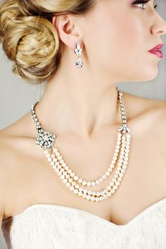 Three strands of silk-knotted genuine freshwater pearls anchored by hidden brooch style clasp. Designer Elsa Corsi