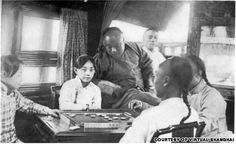 Turn-of-the-century photo shows a young courtesan playing mahjong with customers.