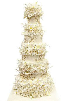 A Towering Wedding Cake With Flowers. No amount of flowers were spared in this Pink Cake Box design that takes wedding cakes to new heights. The floral frenzy is a supreme touch for a traditional winter wedding with a black-tie twist.  See more traditional wedding cakes.
