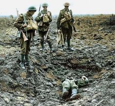 Two soldiers stand looking at the body of a fallen comrade / Jean-Baptiste Tournassoud