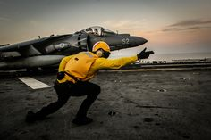 Sailor directs a Harrier II in the Arabian Gulf. by Official U.S. Navy Imagery