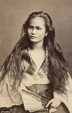 Differences: A Filipino woman is pictured circa 1909 in a loose blouse with a fan and long...