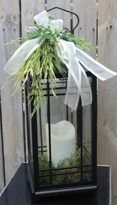 Black lantern with memory candle and winter greens decor