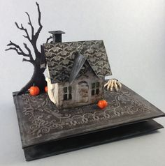 """I've been playing around with the Tim Holtz Vintage dwelling die - still making Halloween houses. This one was painted with gesso, then distressed with black soot. I put it on a """"book"""" base that I made Halloween Village, Halloween Haunted Houses, Halloween House, Fall Halloween, Halloween Decorations, Halloween Parties, Halloween Stuff, Happy Halloween, Christmas Decorations"""