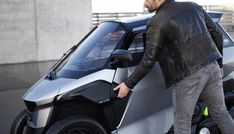The cabin inside Peugeot's tilting PHEV scooter is heated and features seatbelts and an airbag