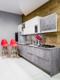 Kuchnia firmy Hacker z frontami białymi o powierzchni satynowej połączona z  frontami imitującymi beton w postaci laminatu Hpl o wybarwieniu jasnoszarym z wieloma pięknymi przecinarkami. Wykończenie ścian to kafle drewno - podobne podkreślające styl skandynawian modern.