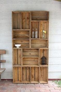 homemade bookcase for the outdoors - with some potted plants and pots scattered around...could be very cool!