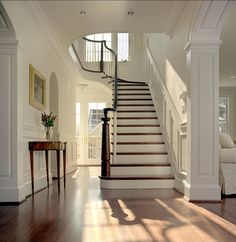 A traditional stair case painted in Benjamin Moore Linen White. Love how the natural light softly streams in through the windows, creates a beautiful, tranquil, diffused light filled entrance.