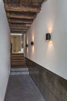 Lampade da parete in corridoio Questa dimora antica si estende su 400 metri quadri e comprende tre saloni, cinque camere da letto, due cucine, due bagni, Di fascino sono anche i corridoi e gli spazi di collegamento tra una zona e l'altra. In questo caso un disimpegno lungo e stretto è arricchito da una boiserie dipinta di nero, da applique dello stesso non colore, da un soffitto in legno a vista. Guarda tutte le foto di questa casa