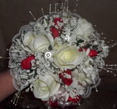 a 7 inch ivory rose nosegay with red rosebuds, pearl sprays and rhinestone stephanotis and a lace backer completes this perfect bridal nosegay