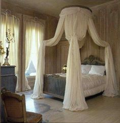 simple, elegant canopy with coordinating curtains, tucked beneath carved cornices