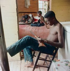 """""""By Any Means Necessary""""…..An African American teen, with his siblings in the background, standing guard with a gun during racial violence in Alabama,1956. Gordon Parks, Photographer."""
