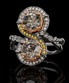 BLACK SWAN INFINITE RING A micro-pave' infinity symbol loops around two Ice Brilliant Diamonds that nest into delicate18k Rose Gold settings detailed by twining vines. Three bezel-set Ice Diamonds on each side attach to a hand-textured double band, detailed with twining vines. Shown in Blackened 18k White Gold with a 1.28 ct & 1.13 ct Ice Brilliant Diamonds