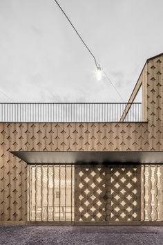 The building's simple exterior is clad in wooden panels with a cut-out pattern resembling interlocking circles, which is influenced by regional decorations.
