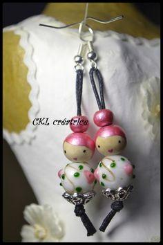 Boucles d'oreilles poupée cheveux roses perles de bois et verre. Les perles en bois sont peintes et vernies à la main. Les boucles d'oreilles mesurent 6,5 cm au total. Perles corps en verre. Coupelles métal argenté. Elles sont livrées dans une jolie petite boîte. Fait main.