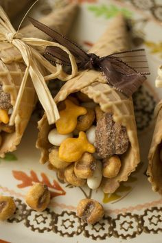 store-bought waffle cones with goodies:   yogurt raisins, roasted corn nuts, candied pecans and goldfish.  Reese's pieces and candy corn for a sweeter version! Tie on a ribbon or raffia bow