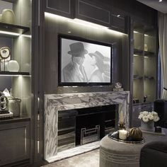 Cosy TV joinery, we added mirror back panelling to create the feeling of more space in an otherwise compact room. The marble fireplace we designed also with smoked mirror panelling is a focal point in the room. Home Fireplace, Fireplace Surrounds, Fireplace Design, Fireplaces, Condo Design, Apartment Design, House Design, Interior Design Living Room, Living Room Decor